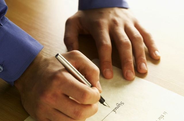 Man signing a legal document prepared by attorney in Russellville, AR