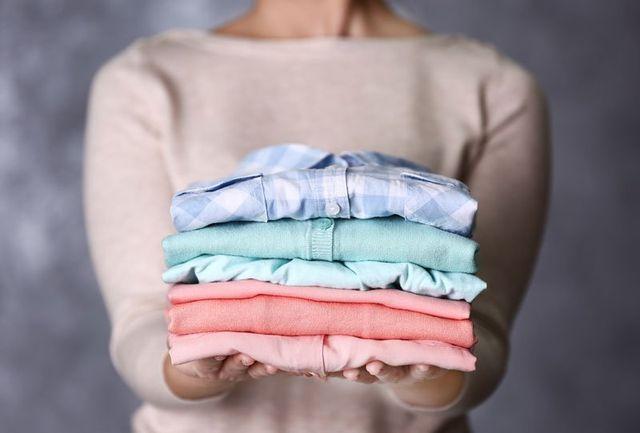 una donna sta mostrando delle camicie piegate di diversi color