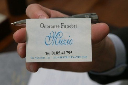 una mano con un biglietto da visita con scritto Onoranze Funebri Muzio
