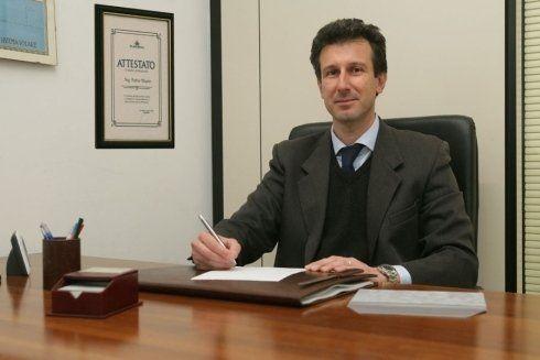 un uomo  con un completo seduto alla scrivania in ufficio