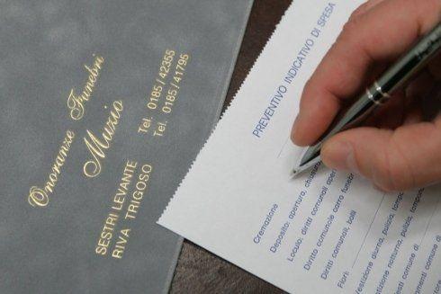 una mano con una penna mentre compila un preventivo indicativo di spese per cremazione