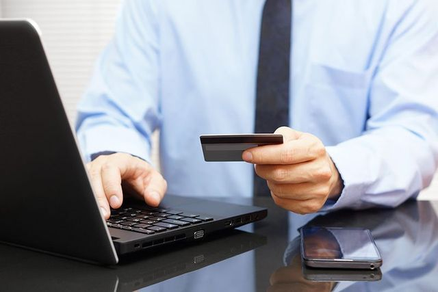 Businessman is using credit card for online payment on laptop