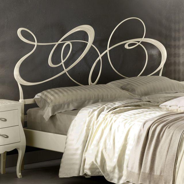un letto con una testata di color giallo e un comodino in legno