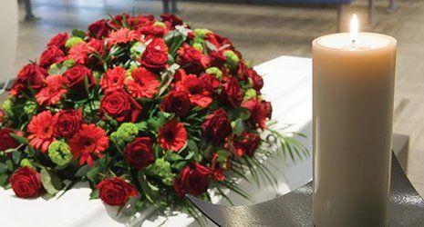 Un bouquet di crisantemi di color rosso su una bara di colore bianco e una candela bianca accesa
