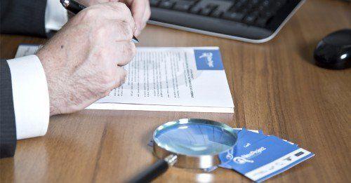 Uomo con penna in mano, firma documenti e accanto a lui una lente di ingrandimento