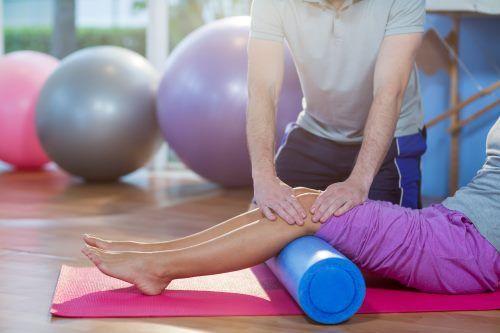 Fisioterapista che assiste la donna mentre si esercita sulla stuoia di esercitazione in clinica