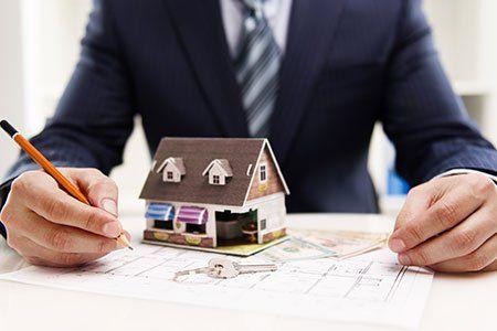 Vista della modello di una casa, una chiave, e una mano con un matita su un piano