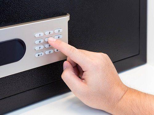 una mano che digita i tasti di una cassaforte