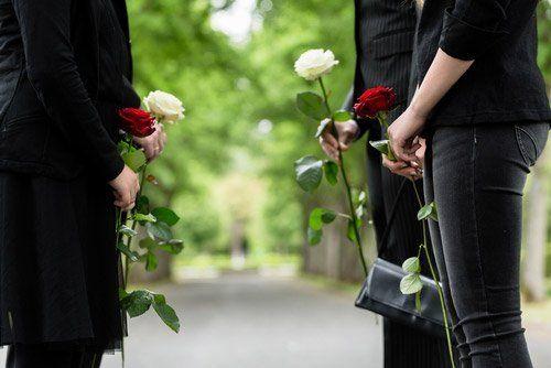 persone in lutto con delle rose