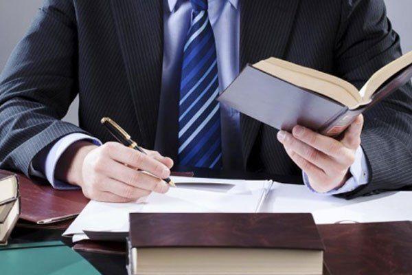 avvocato seduto alla scrivania in ufficio e di firmare un contratto