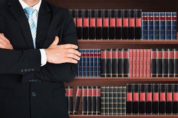 primo piano di avvocato maschio con braccio attraversato in piedi davanti a mensola del libro