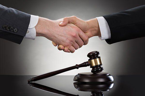 primo piano di due uomini d'affari si stringono la mano davanti a martello