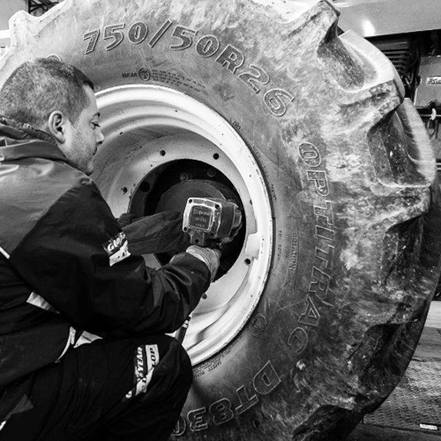 Meccanico che avvita i bulloni di una ruota 750/50R26