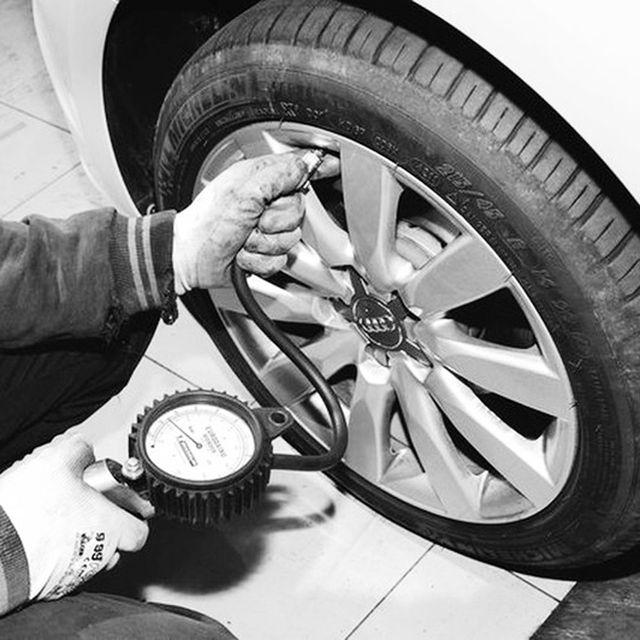 Mano di tecnico che misura pressione a un pneumatico.