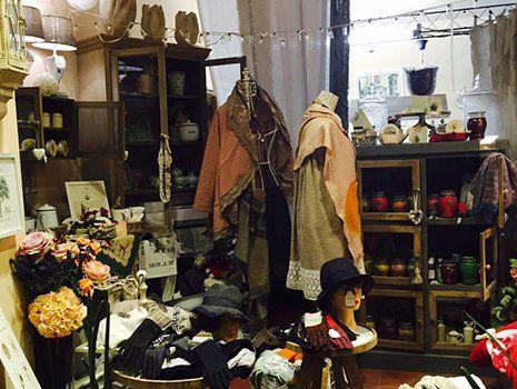vestiti, scaffali in legno e una vetrina con dei barattoli