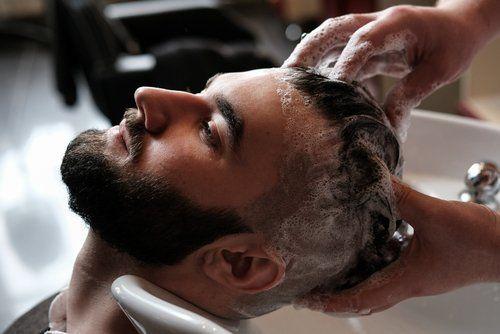 ragazzo con barba fa lo shampoo dal parrucchiere
