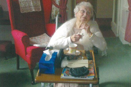 one of our female residents with tea on a tray