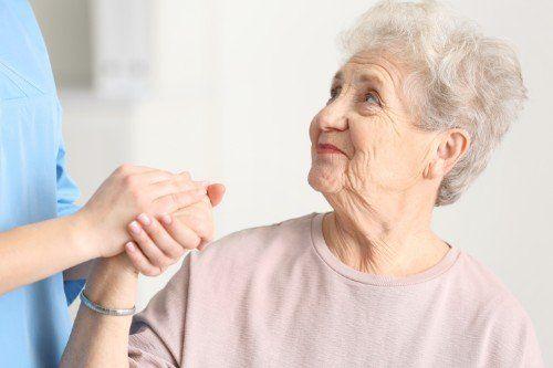 una donna anziana sorride mentre riceve assistenza