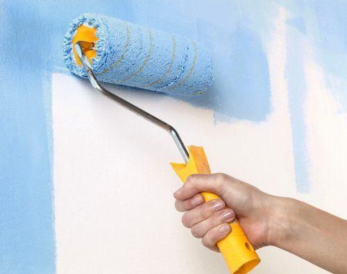 una mano con un rullo che imbianca un muro di azzurro
