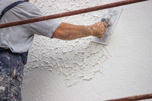 un imbianchino che usa una spatola su un muro