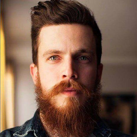 un ragazzo con dei capelli castani con riga da parte e barba folta