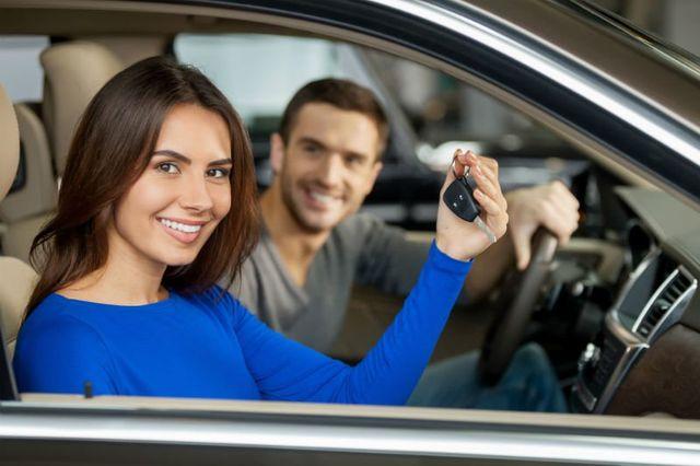 Bella giovane coppia seduta ai sedili anteriori della loro nuova auto mentre la donna mostrando chiavi e sorridente