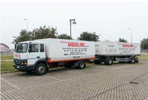 due camion parcheggiato sulla strada scritto su UGOLINI-IVECO 145-17 R