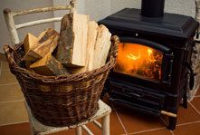 A basket of logs on a chair beside a wood burning stove