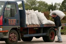 A man loading sacks of coal onto a lorry
