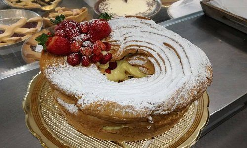 una torta con crema pasticcera, zucchero a velo e fragole