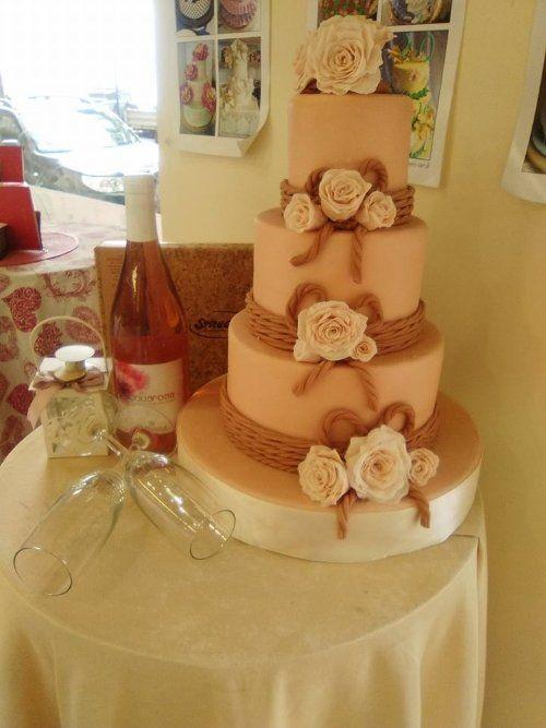 una torta a tre piani con glassa rosa, fiori una bottiglia accanto