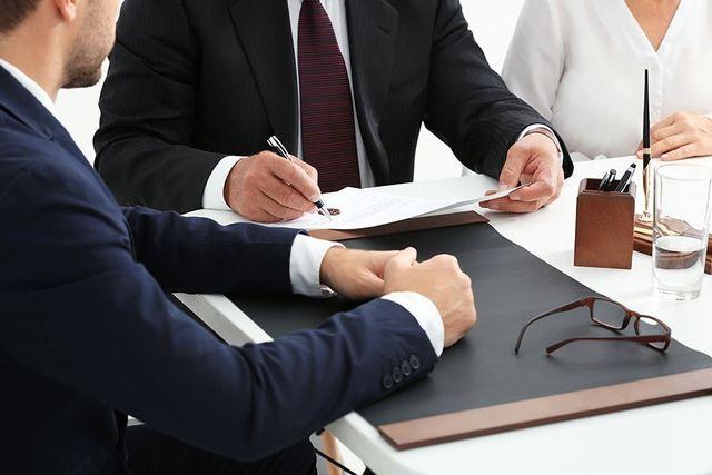 un uomo con una penna e un foglio in mano e accanto altre persone sedute