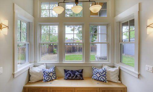 delle finestre e davanti una panca di legno con dei cuscini