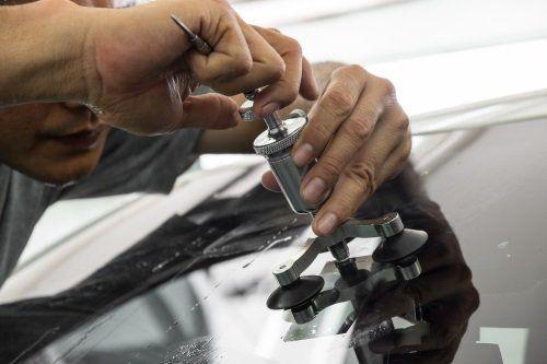 Due mani che riparano un parabrezza