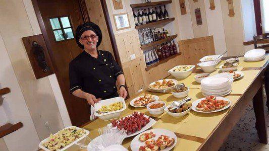 Il padrone del ristorante che prepara il buffet