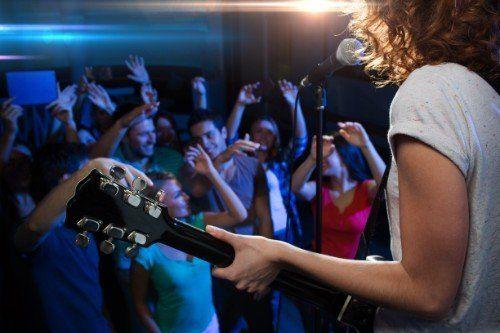 donna con chitarra e persone che ballano