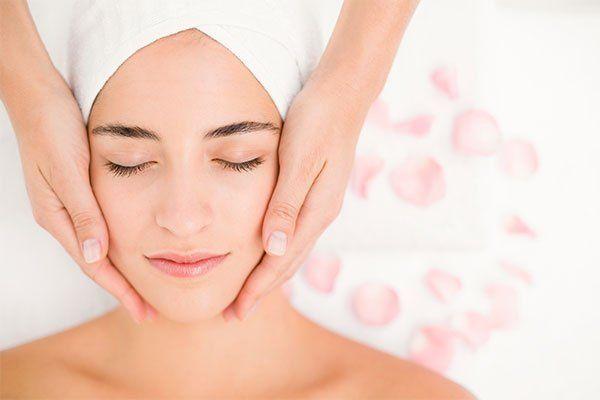 Due mani che tengono il viso di una donna con un asciugamano in testa