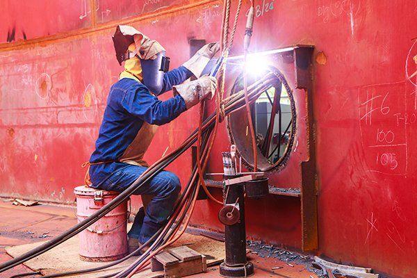 un operaio con una tuta protettiva e una torcia vicino a un buco nel muro con dei cavi a vista