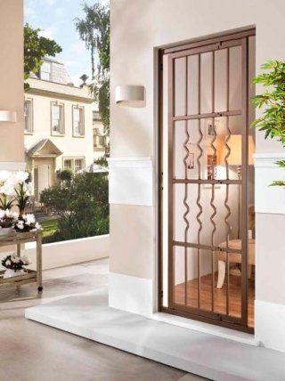 una finestra con una griglia di color marrone e vista delle altre case accanto