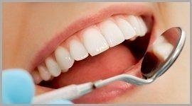 mano del dentista tiene uno specchietto per una visita dentistica a una donna