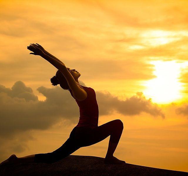 una ragazza durante una posizione yoga durante il tramonto