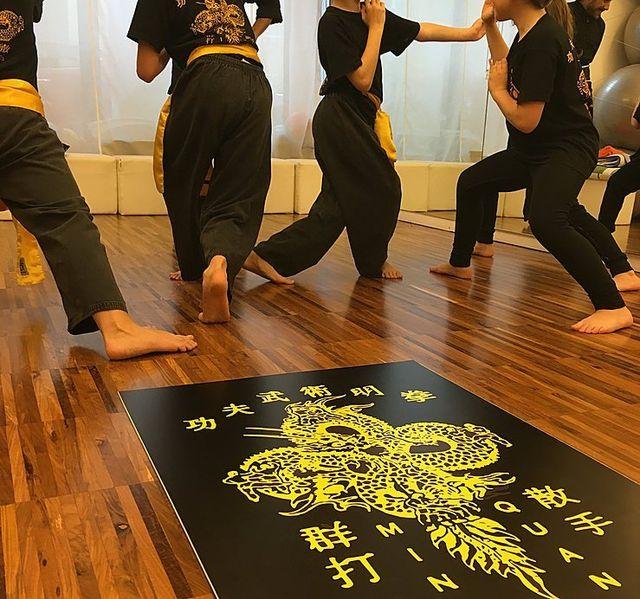 un gruppo di persone vestite con delle magliette nere con su degli ideogrammi gialli mentre svolgono le arti marziali