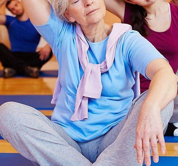 una donna anziana con una maglietta azzurra sciarpa rosa e pantaloni grigi a gambe incrociate mentre svolge degli esercizi e dietro altre persone che svolgono lo stesso esercizio
