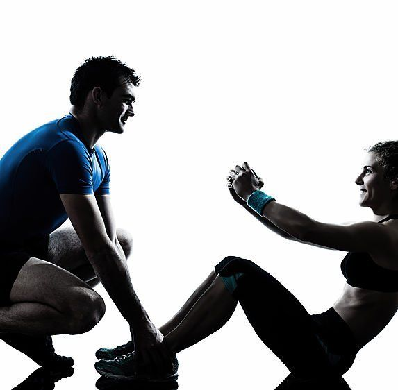 un ragazzo con una maglietta blu chinato a terra mentre tiene i piedi a una ragazza che sta facendo degli addominali