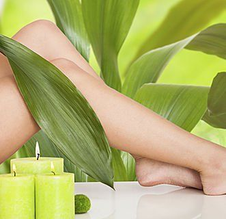 vista di due gambe di una donna tra delle grandi foglie verdi e accanto dei lumini accesi color verde mela