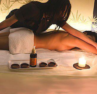 un uomo senza vestiti sdraiato a pancia in giù con un asciugamano alla vita e una donna che le pratica un massaggio alla schiena