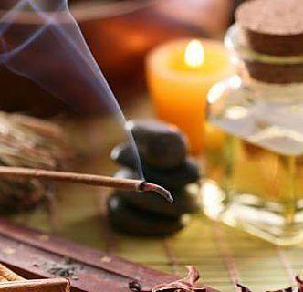 vista di un bastoncino di legno con della cenere e del fumo e dietro delle essenze