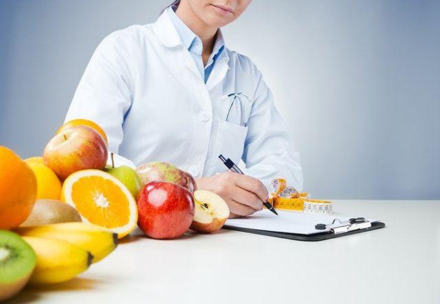 Nutrizionista prende appunti con della frutta sul tavolo