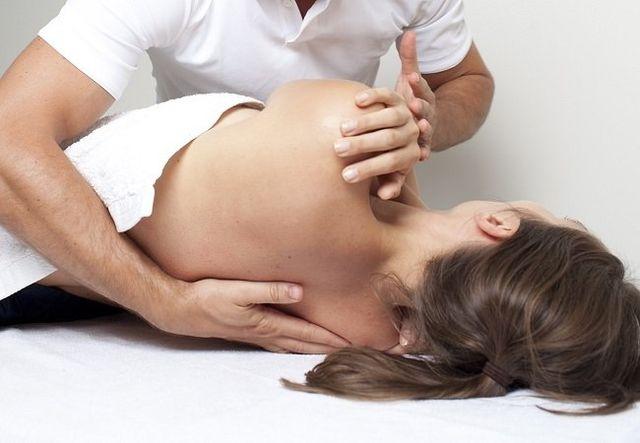 Fisioterapista effettua operazione palpatoria su donna