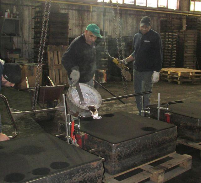 Due uomini vestiti in abiti scuri che versano metallo in una fonderia a terra
